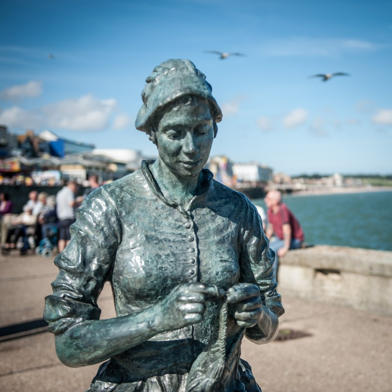 The Gansey Girl - This bronze sculpture, has historic and sentimental meaning in that she reflects the fishing history in Bridlington as well as the families in the town. She depicts a young woman sitting on a plinth knitting a gansey, a traditional jumper that contains a rich pattern of symbolism passed down through generations of fishing families.